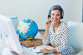 Smiling travel agent sitting at her desk