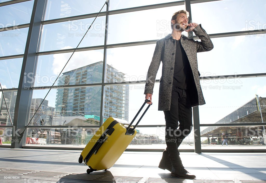 Smiling travel man walking and talking on mobile phone stock photo