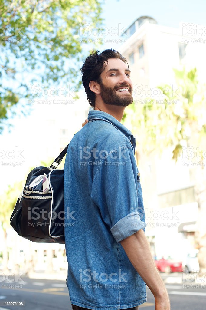 Smiling traveling man with bag on the street stock photo