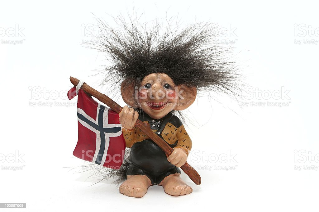 A smiling troll doll with wild hair holds the flag of Norway stock photo