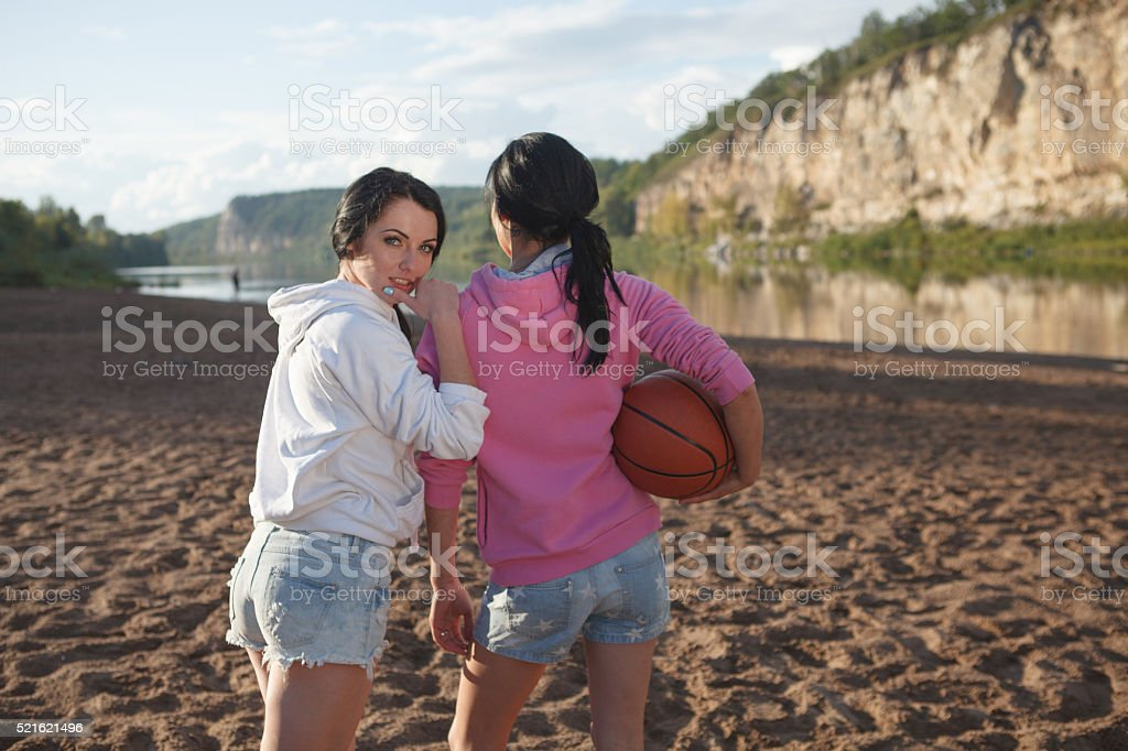 Smiling two women holding a basketball stock photo