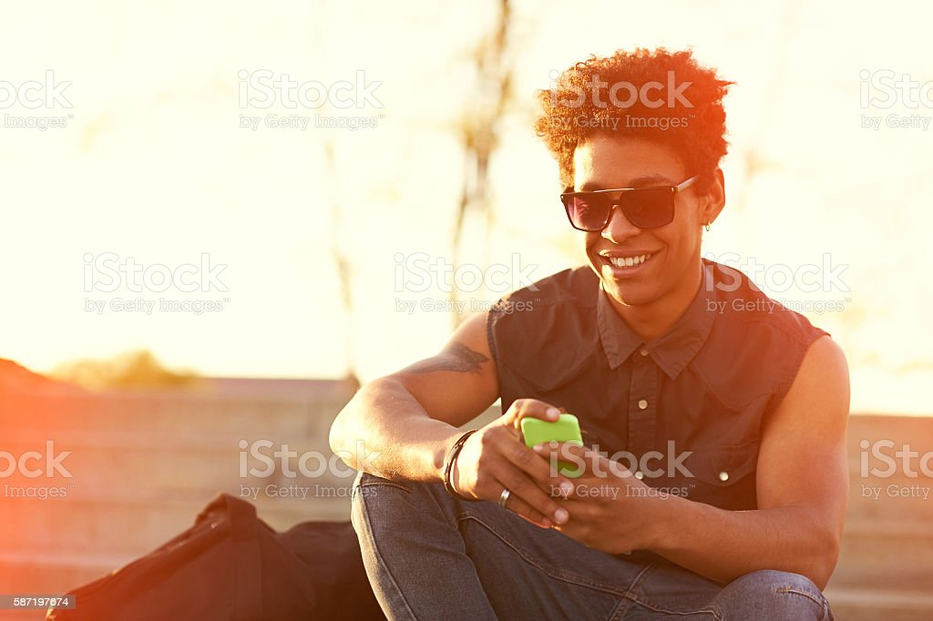 smiling urban hipster young man using smart phone stock photo