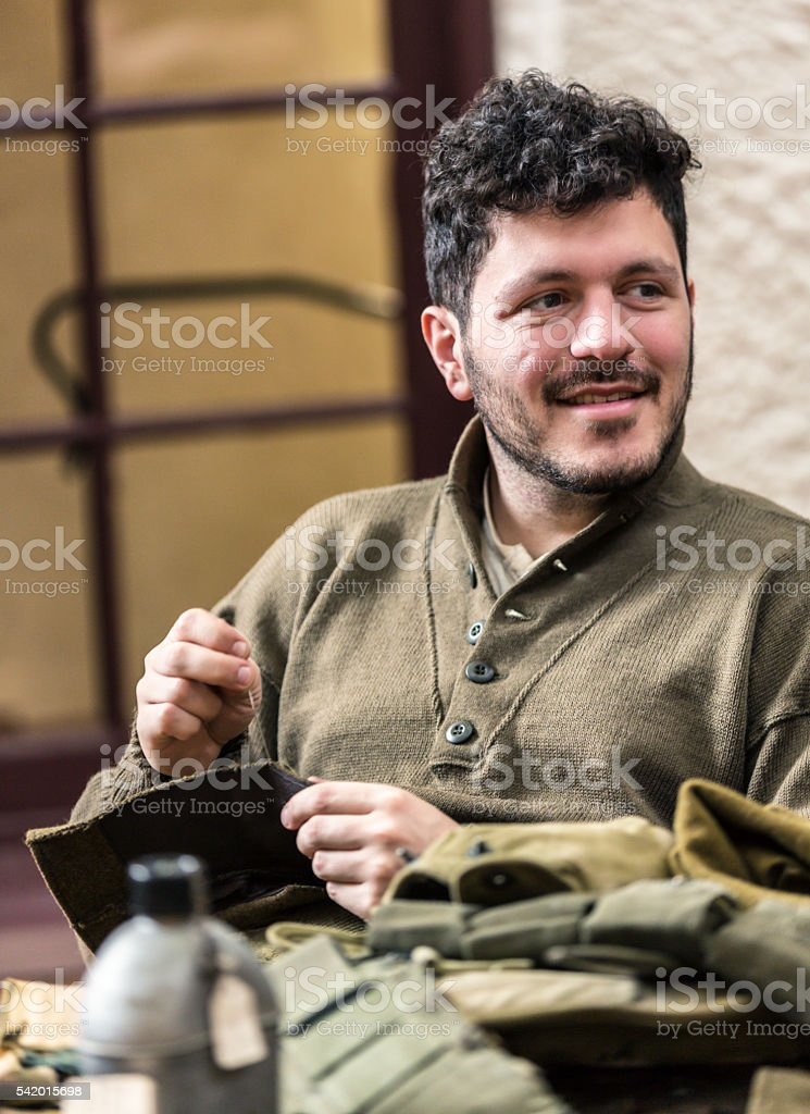 Smiling US Army WWII Soldier Sewing Uniform Looking Sideways stock photo