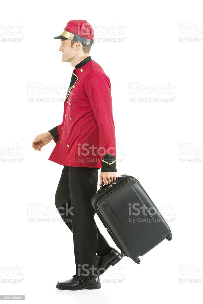 Smiling valet walking with suitcase royalty-free stock photo