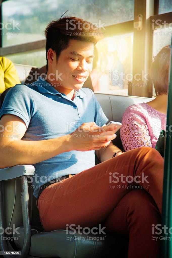 Smiling Vietnamese male student text messaging on bus Hanoi stock photo