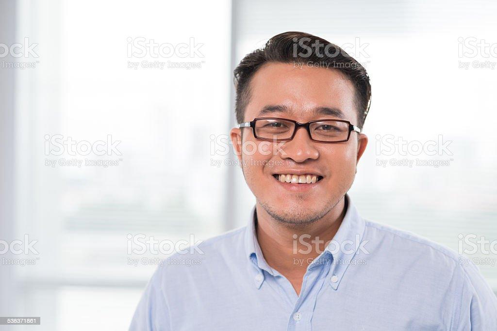 Smiling Vietnamese man in glasses stock photo