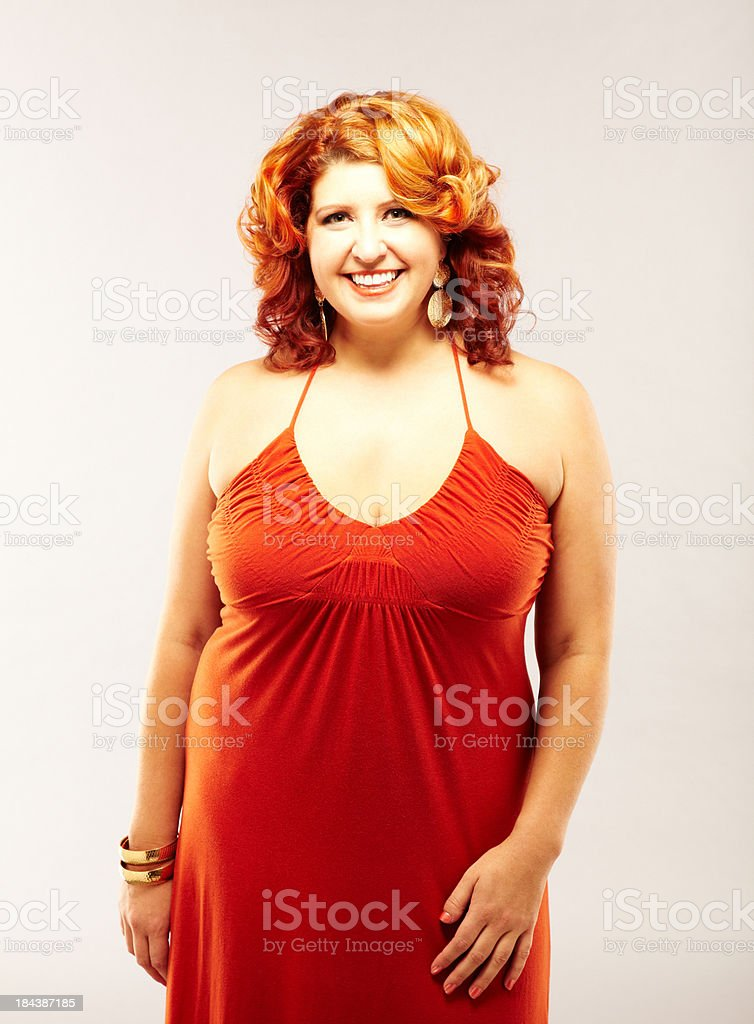 Smiling Voluptuous Red-Haired Woman Wearing Red Dress royalty-free stock photo