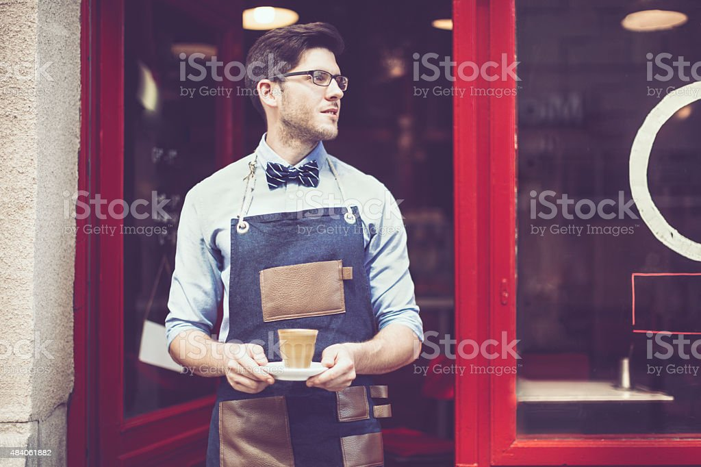 Smiling waiter is holding an espresso stock photo