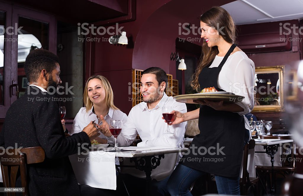 Smiling waitress and guests at the table stock photo