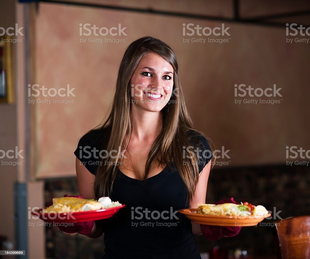 Smiling waitress carrying plates of food royalty-free stock photo