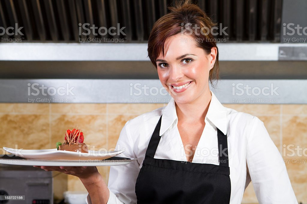 Smiling waitress holding a plate with dessert royalty-free stock photo