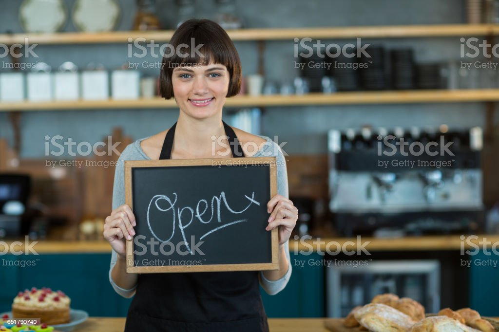 Smiling waitress showing slate with open sign royalty-free stock photo