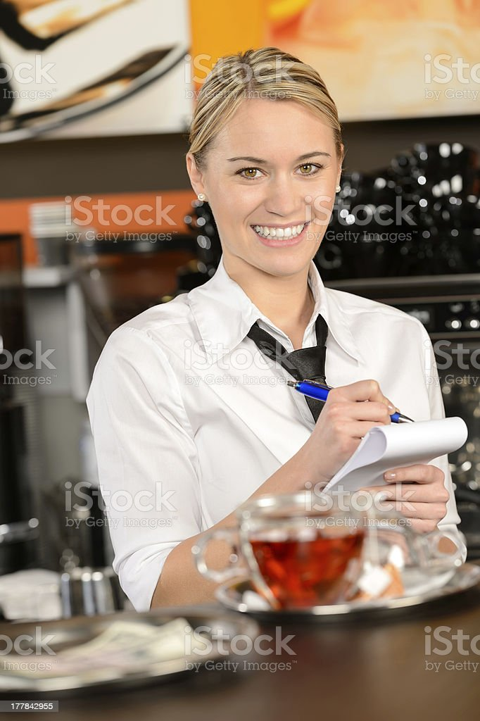 Smiling waitress taking order in coffee house royalty-free stock photo