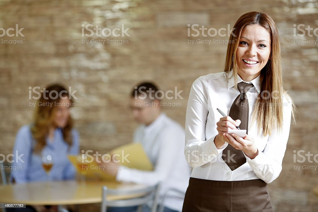 Smiling Waitress Writing In Order Pad At Restaurant. stock photo