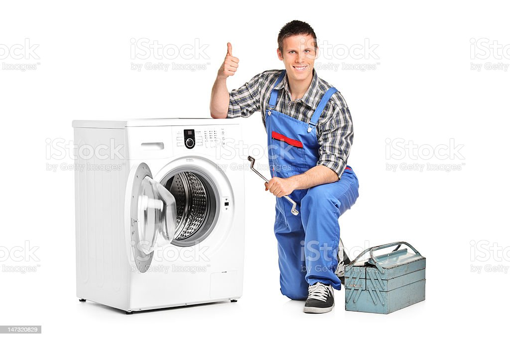 Repairman giving thumb up next to a machine stock photo
