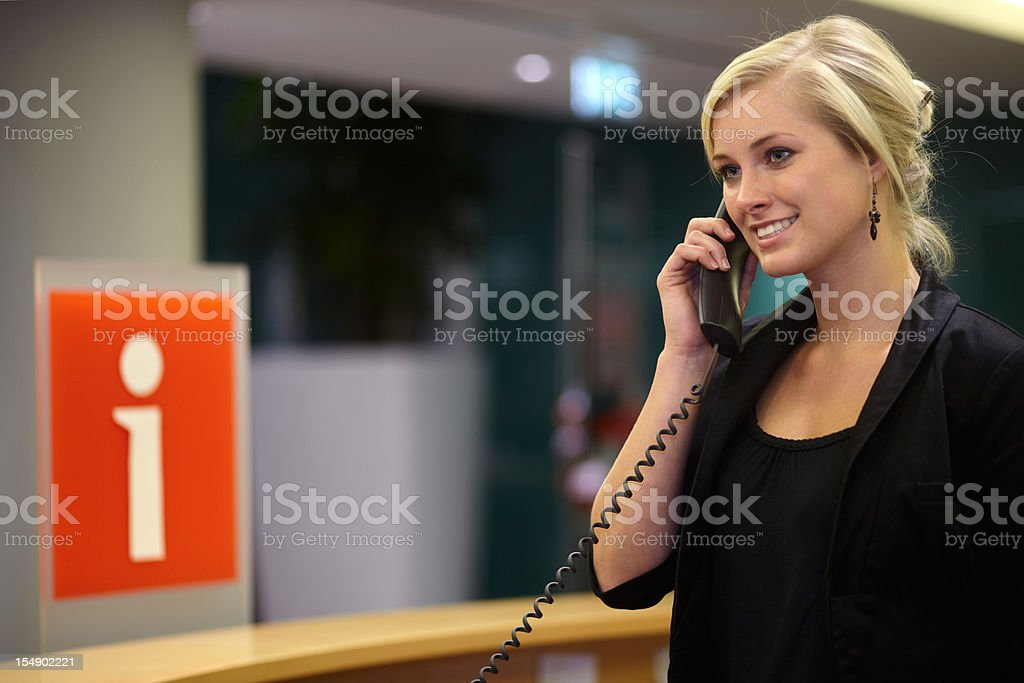 Smiling, welcoming woman on the phone at an information desk stock photo