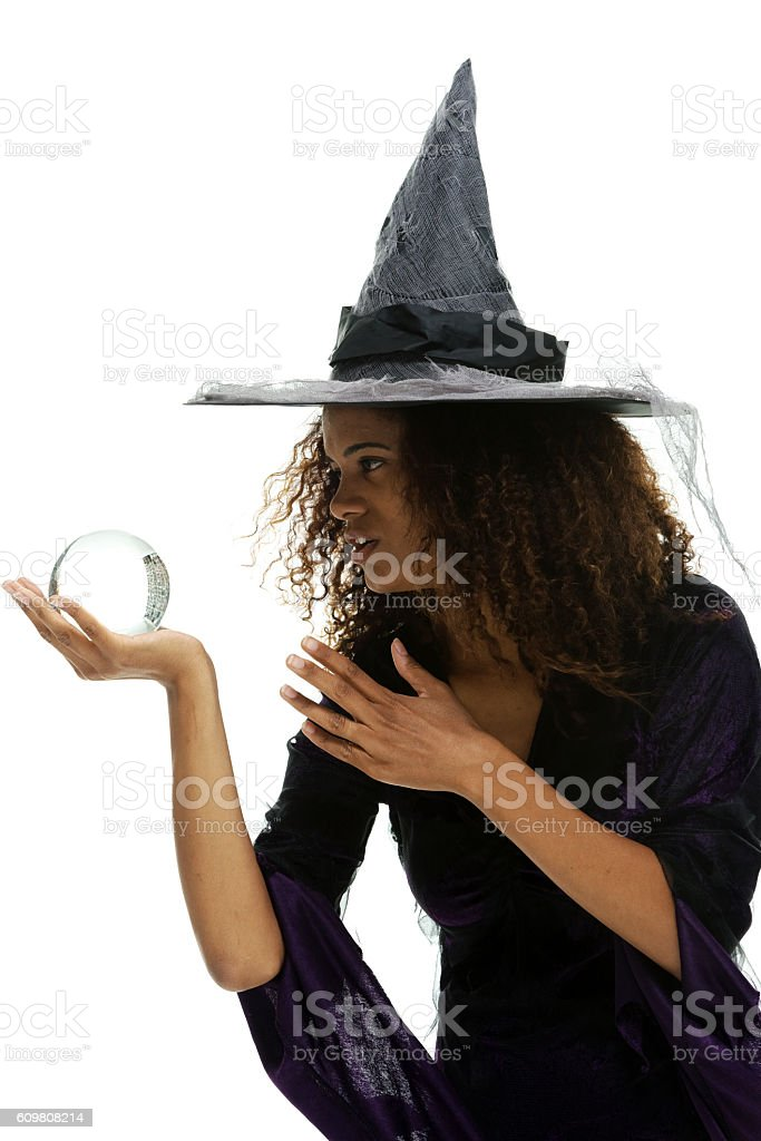 Smiling witch holding crystal ball stock photo