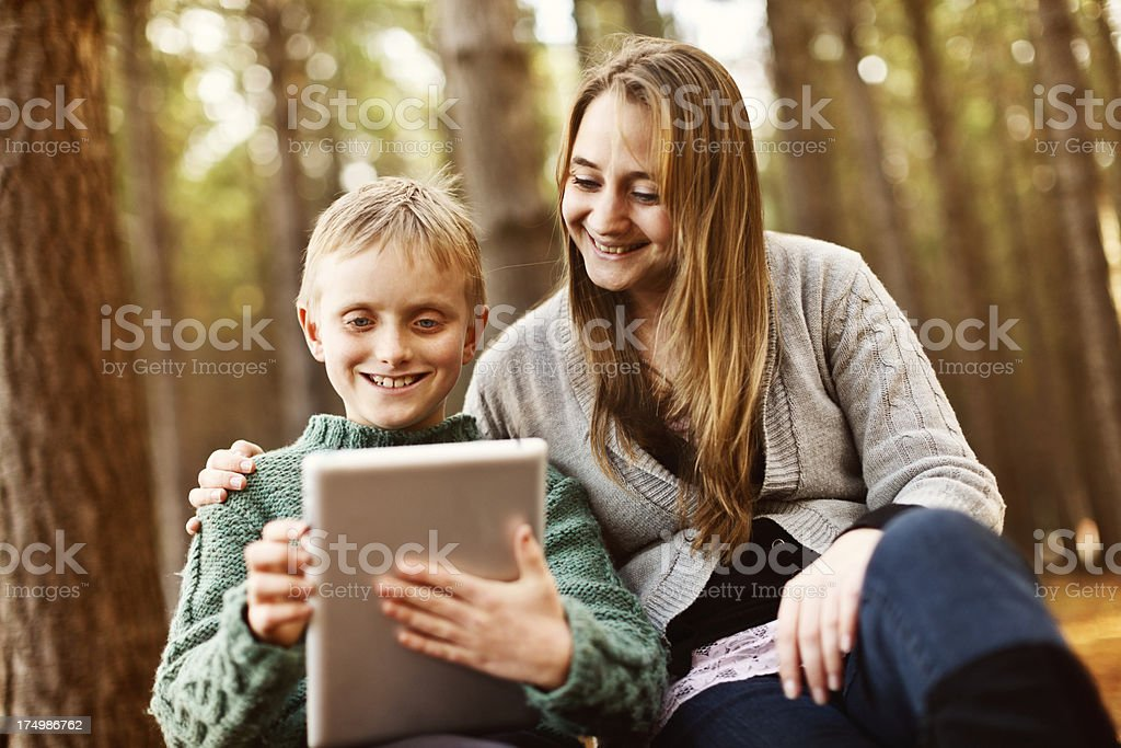 Smiling woman and boy studying digital tablet outdoors stock photo