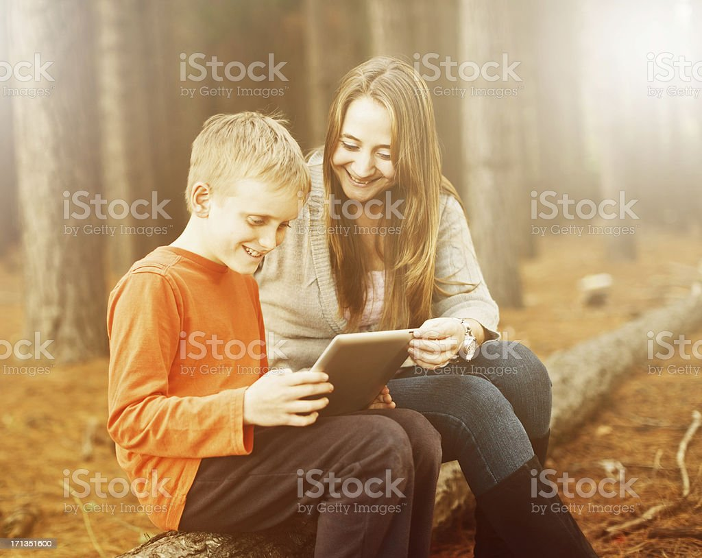 Smiling woman and boy with tablet-style pc in afternoon sunshine stock photo