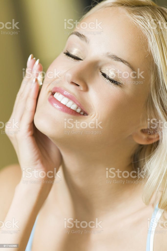 Smiling woman applying cream on face at home royalty-free stock photo