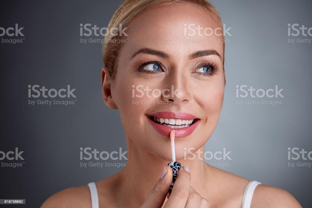 Smiling woman applying lip-gloss on lips stock photo