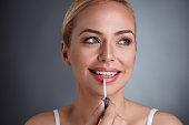 Smiling woman applying lip-gloss on lips