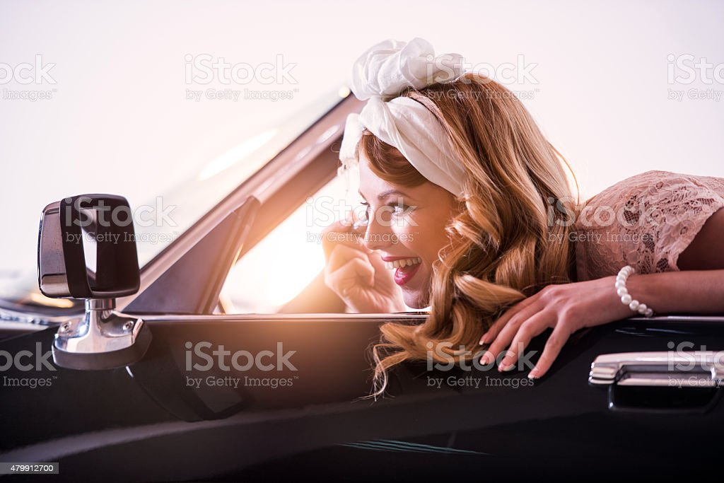 Smiling woman applying make-up in convertible car at sunset. stock photo