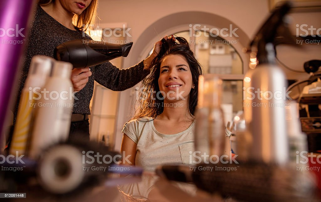 Smiling woman at hair salon getting her hair dried. stock photo