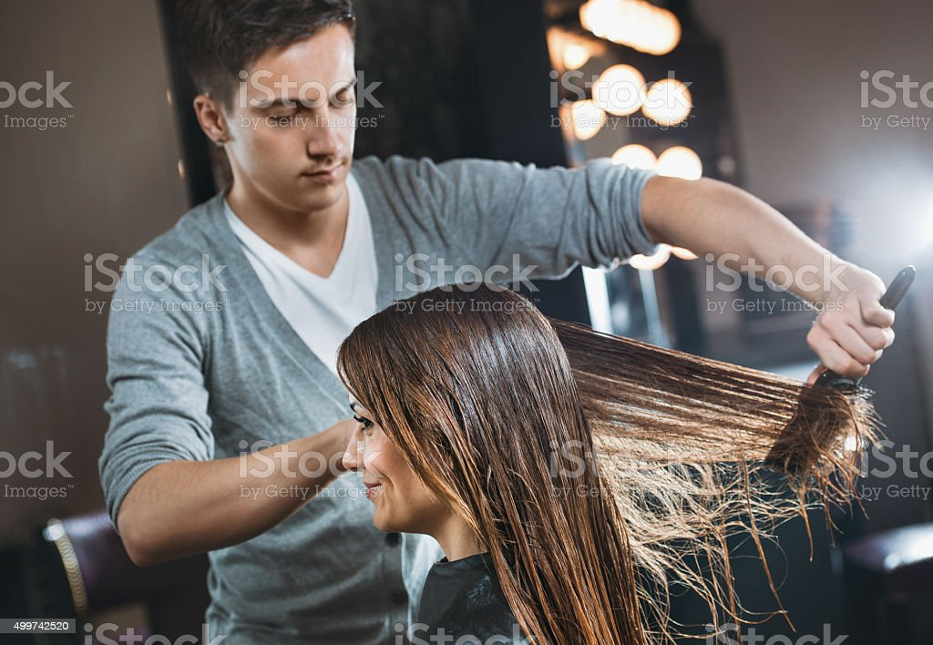 Smiling woman at hairdresser salon getting her hair styled. stock photo