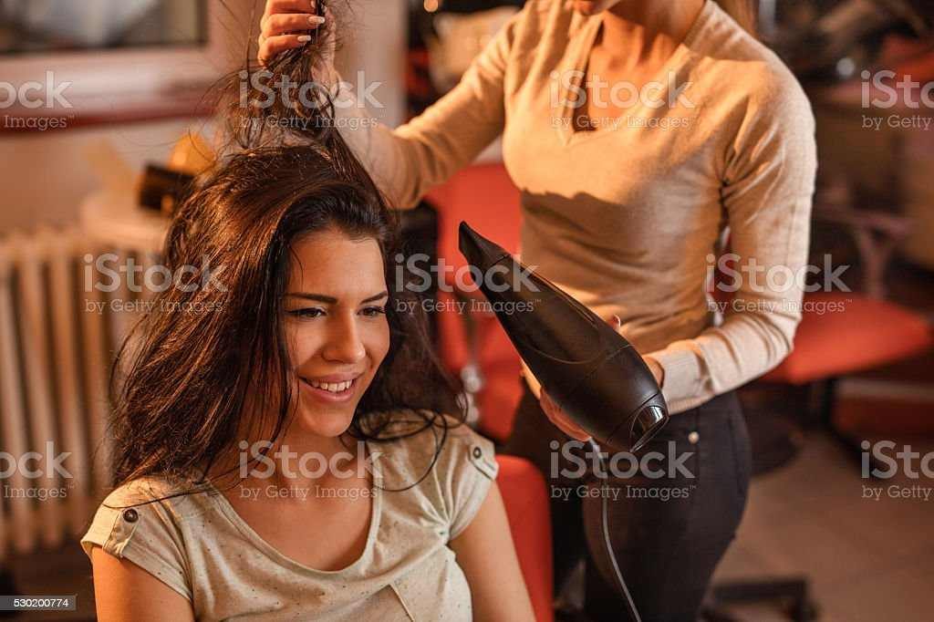 Smiling woman at hairdressers getting her hair dried. stock photo