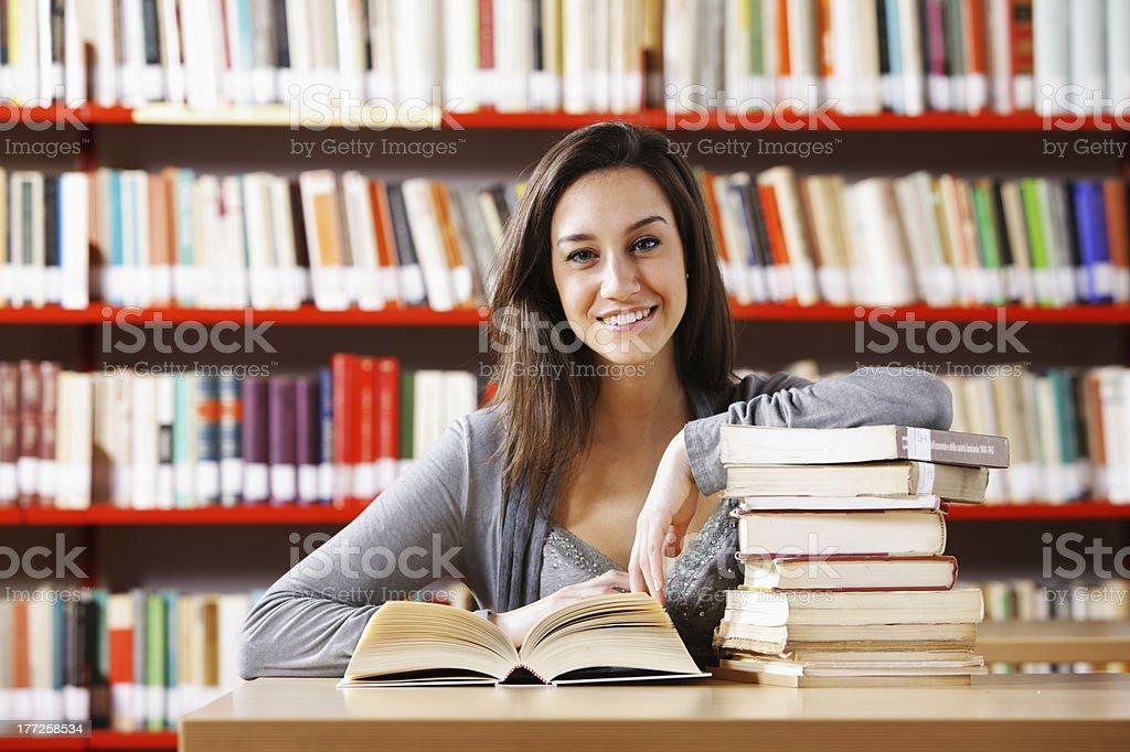 Femme souriante dans la bibliothèque avec une pile de livres photo libre de droits