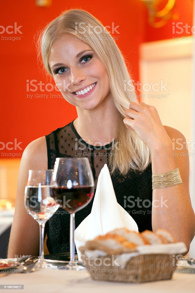 Smiling Woman at Table Having Bread and Wine. stock photo