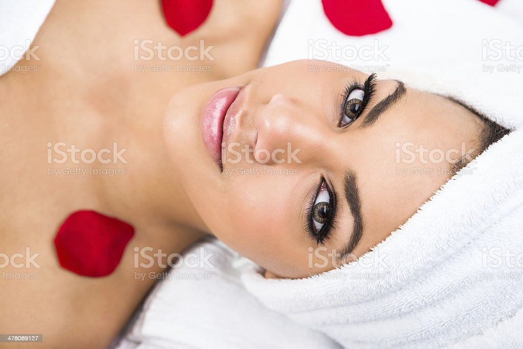 Smiling woman at the spa with rose petals royalty-free stock photo