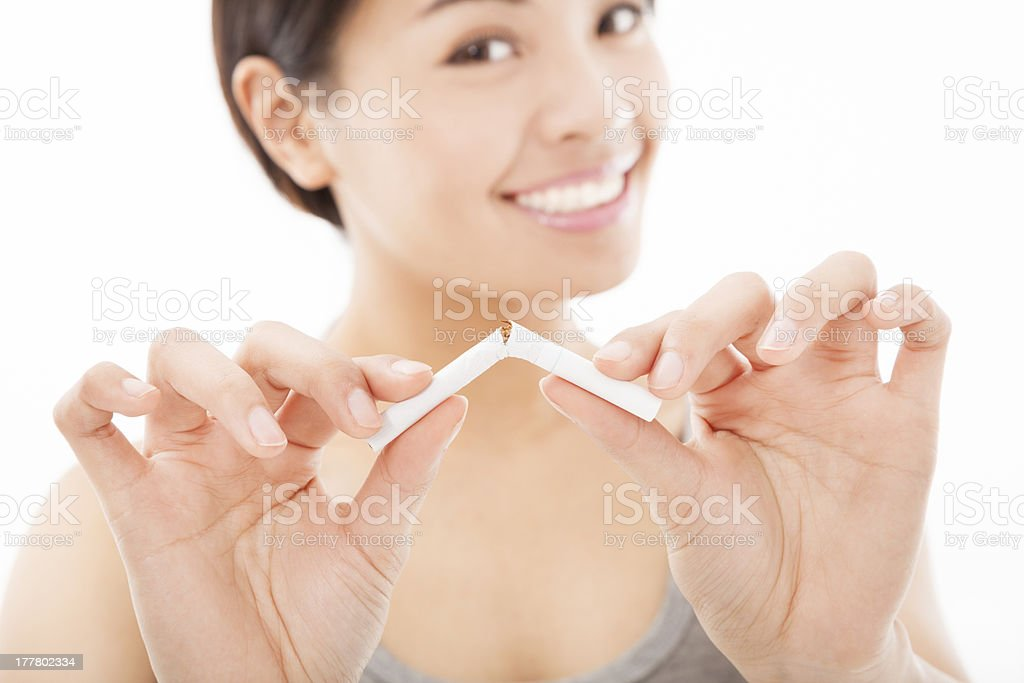 smiling woman breaking cigarette stock photo