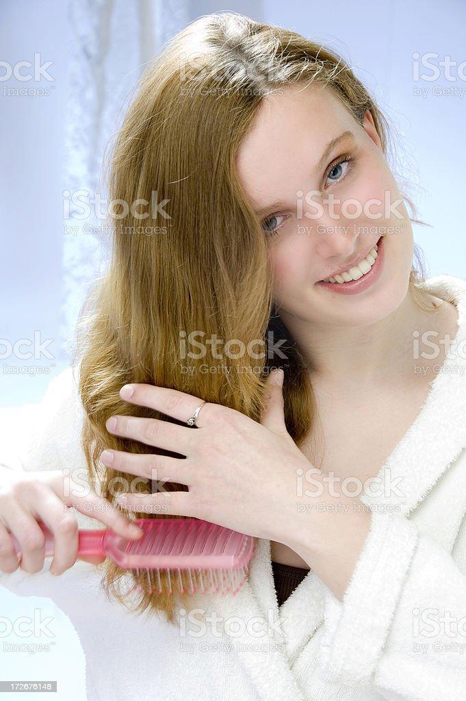 smiling woman brushing hair royalty-free stock photo