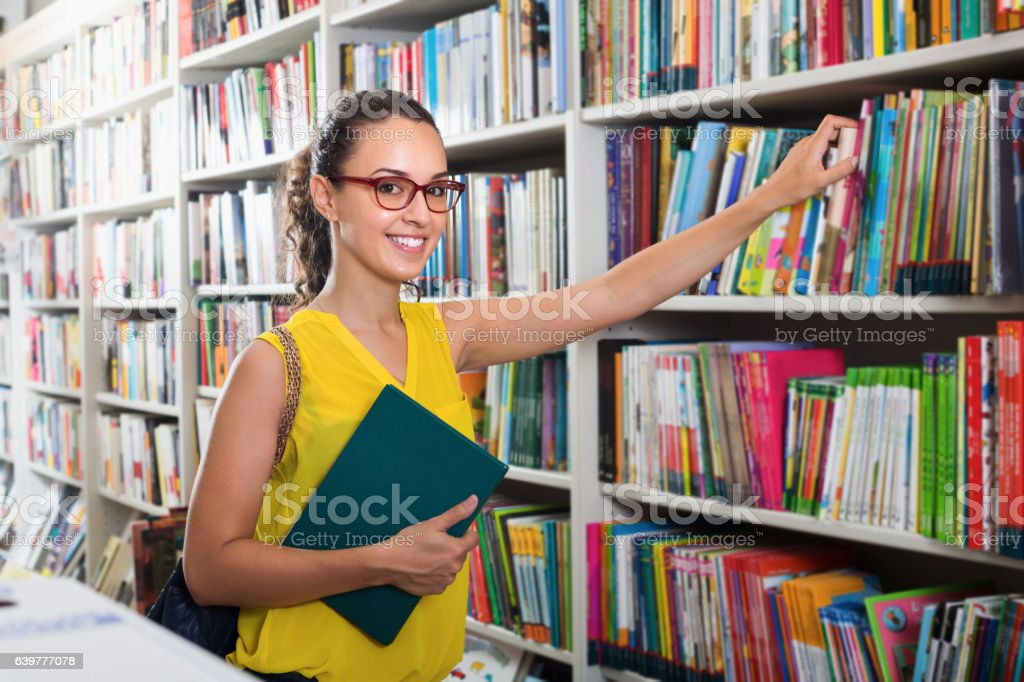 Smiling woman buying books in hard cover stock photo