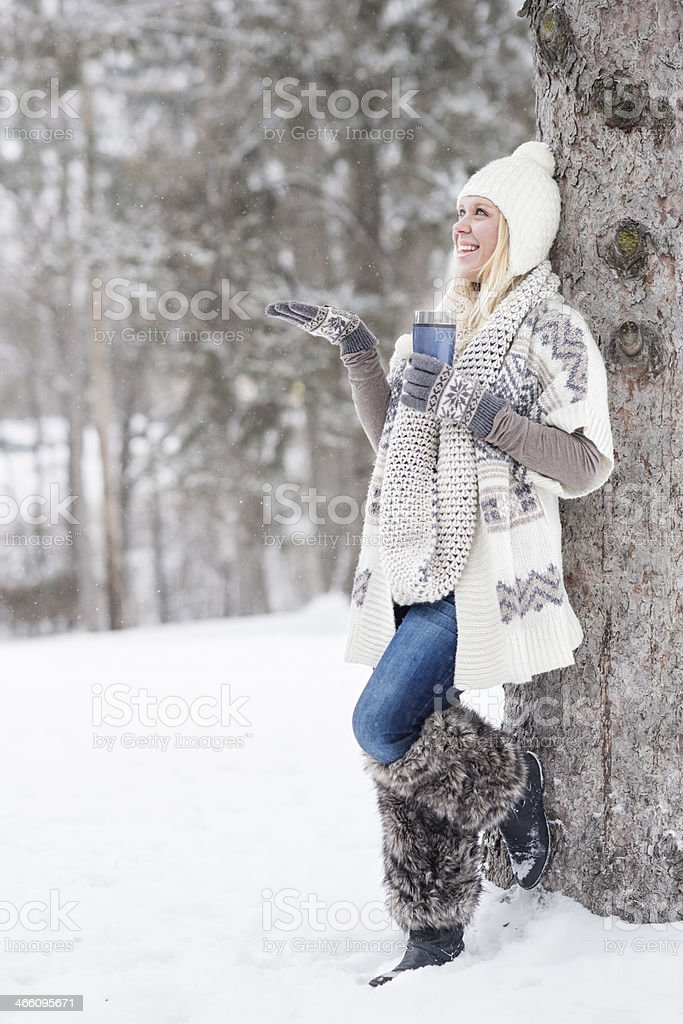 Smiling woman catches snowflakes in hand stock photo