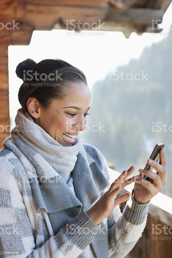 Smiling woman checking cell phone on cabin porch stock photo