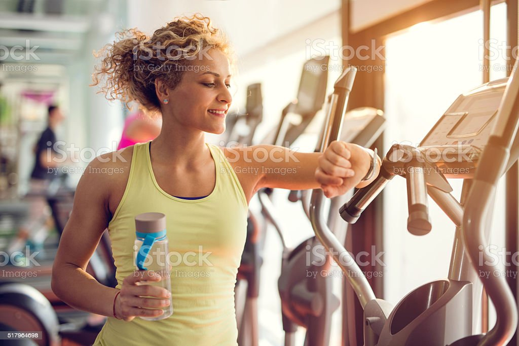Smiling woman checking time on wristwatch in a gym. stock photo