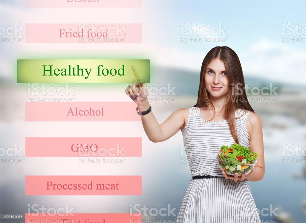 Smiling woman choose healthy food on futuristic screen stock photo