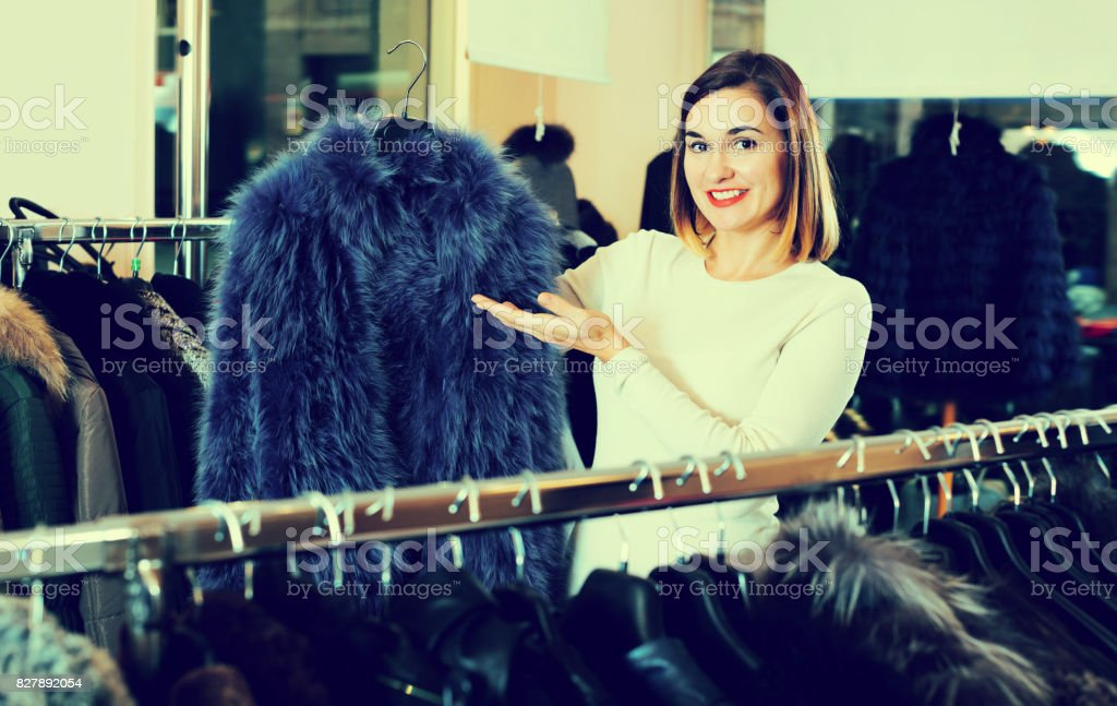 Smiling woman choosing blue fur coat stock photo