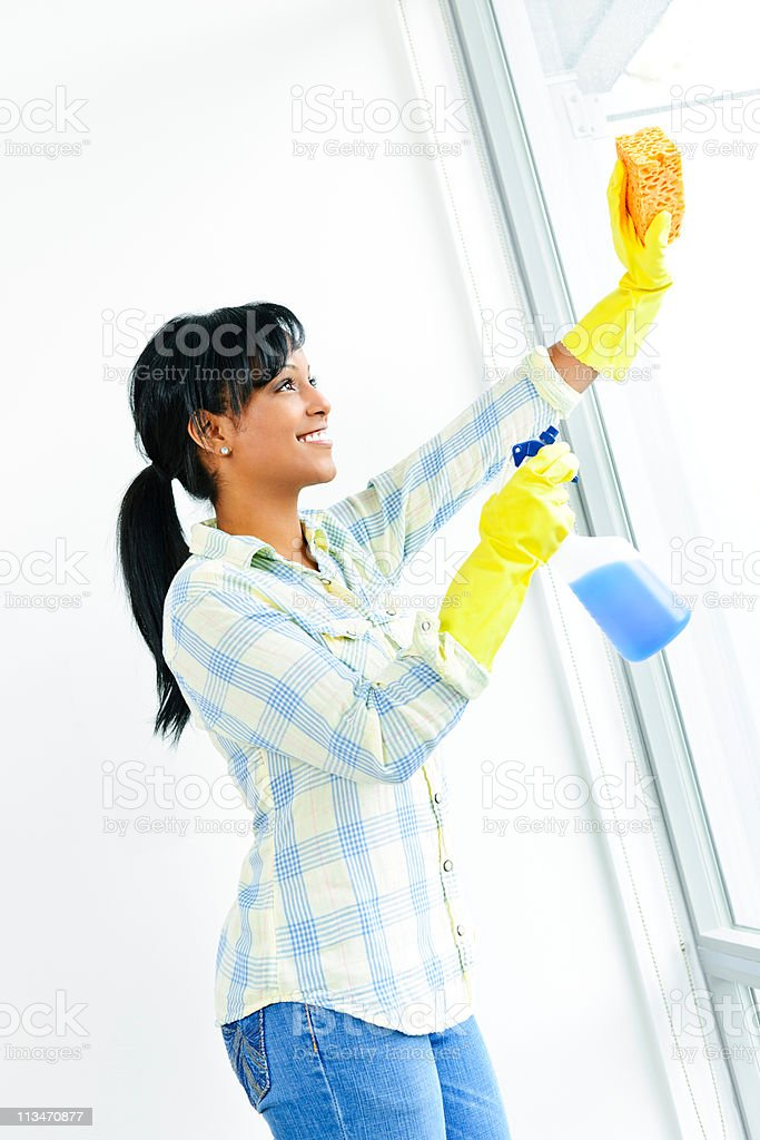 Smiling woman cleaning windows and wearing cleaning gloves royalty-free stock photo