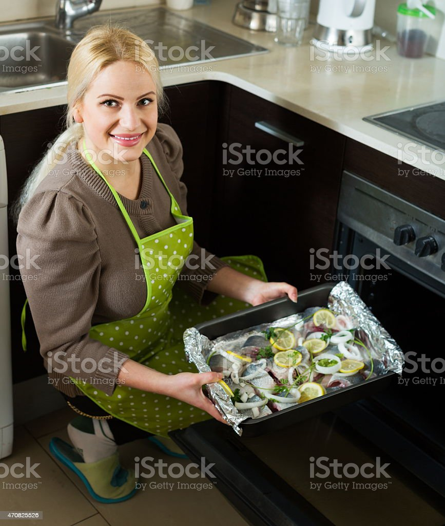 Smiling woman cooking fish stock photo
