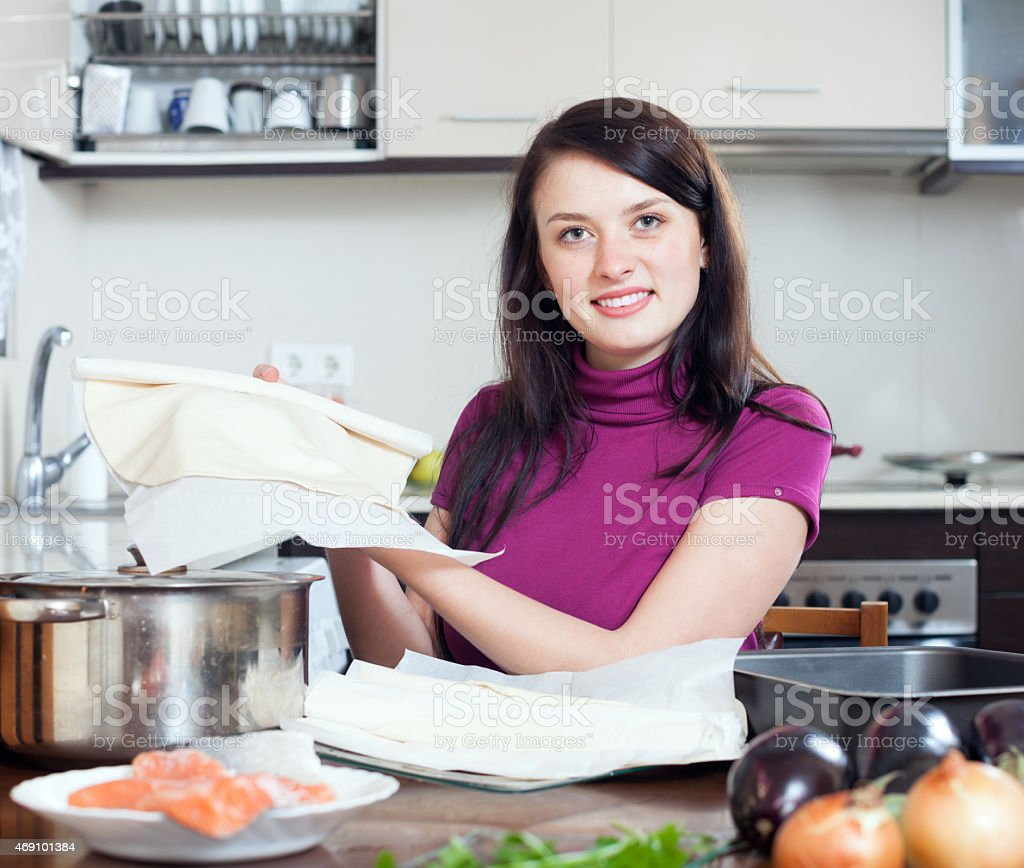 Smiling woman cooking fish pie with  store-bought dough stock photo