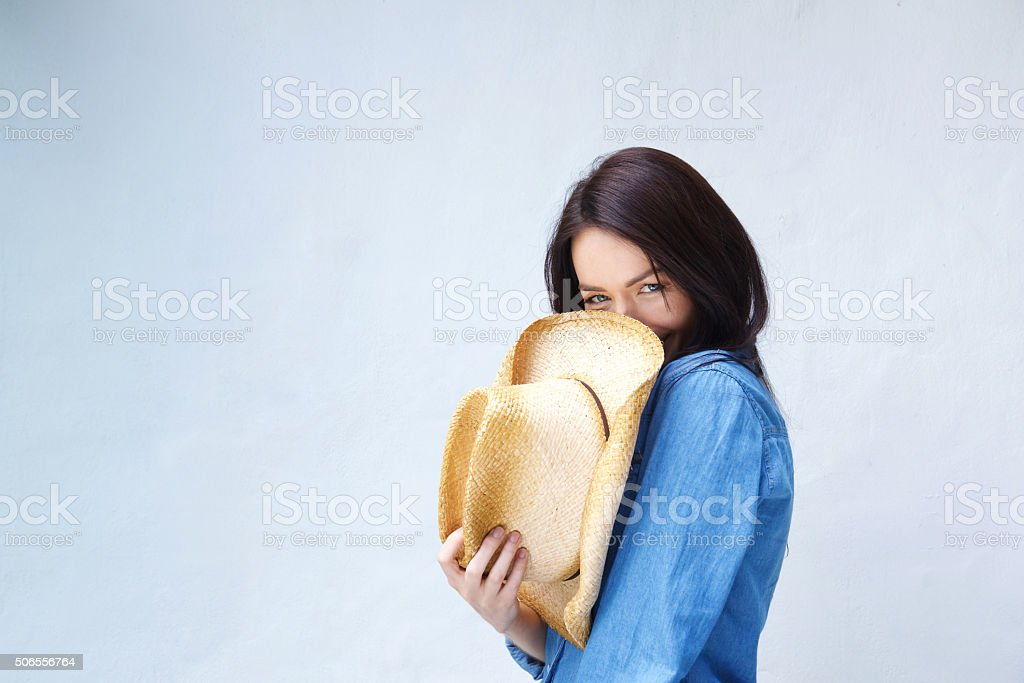 Smiling woman covering face with cowboy hat stock photo