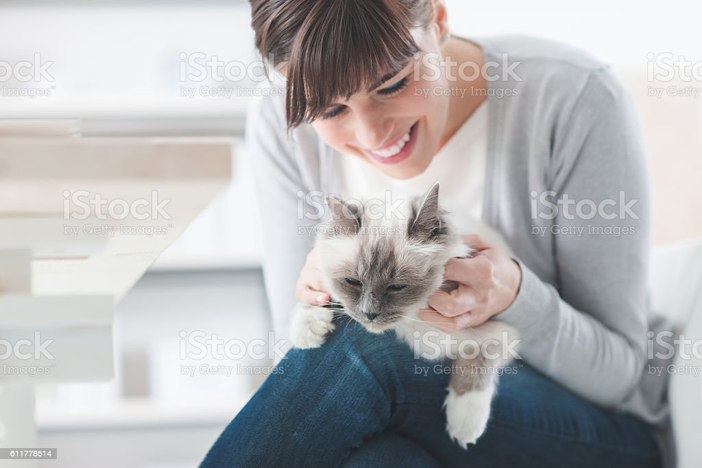 Smiling woman cuddling her cat stock photo