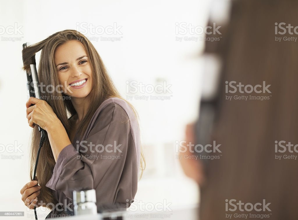 smiling woman curling hair with straightener stock photo