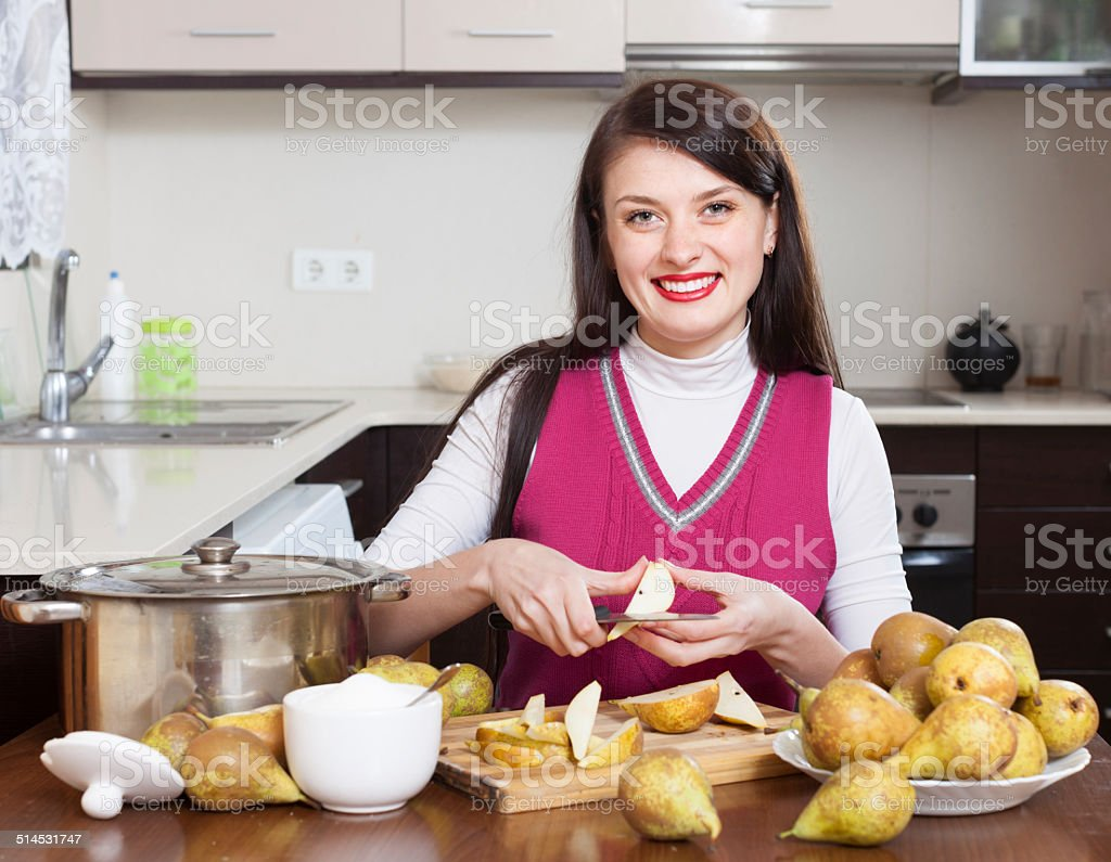 Smiling woman cutting pears for pear jam stock photo