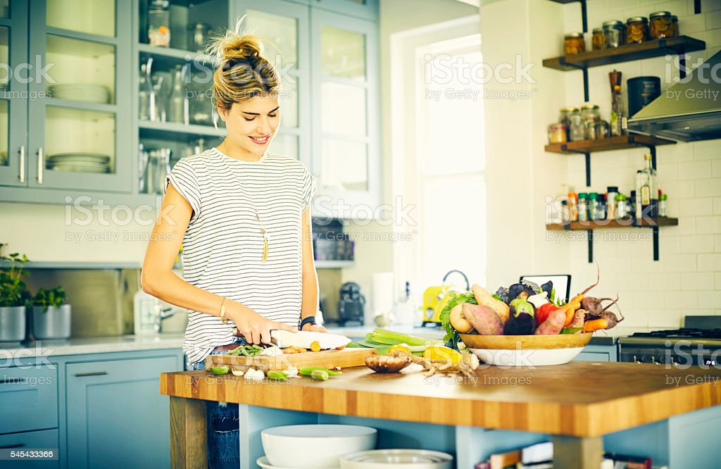 Smiling woman cutting vegetables with knife at kitchen island stock photo