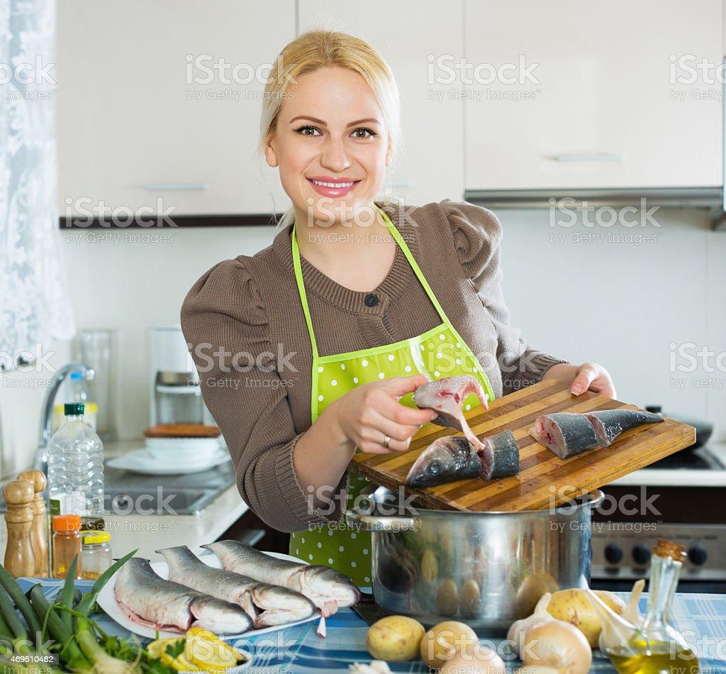 Smiling woman cutting white fish stock photo